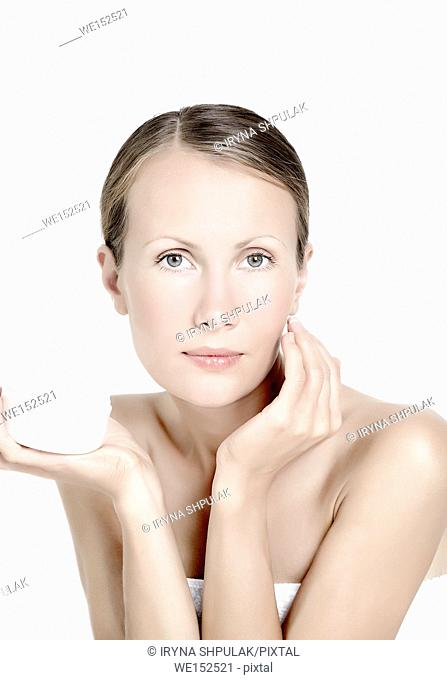 Young woman holding pot of skin cream