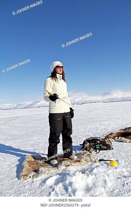 Young woman ice fishing