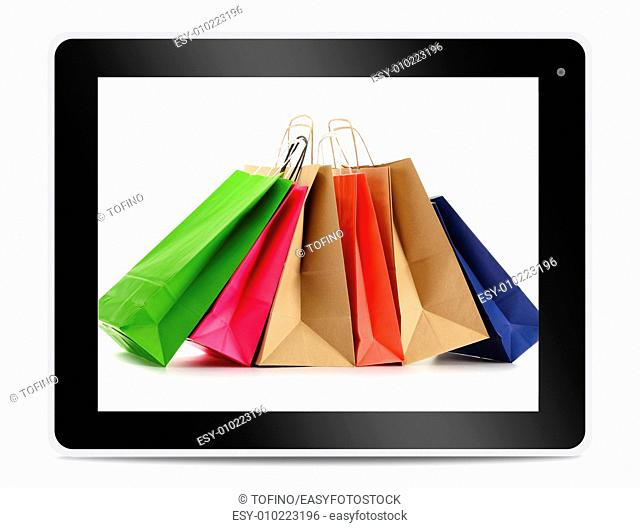 Paper shopping bags on computer tablet screen. Shopping online. E-commerce