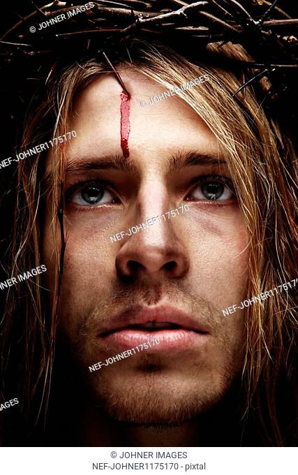 Young man as Jesus wearing crown of thorns, studio shot