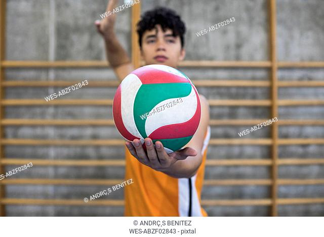 Man holding a volleyball ball prepared to start a game during a volley match