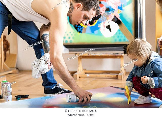 Male painter and toddler girl creating painted art work together