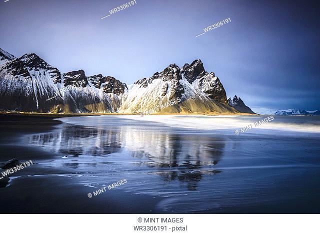 Ocean waves on beach under snowy mountains