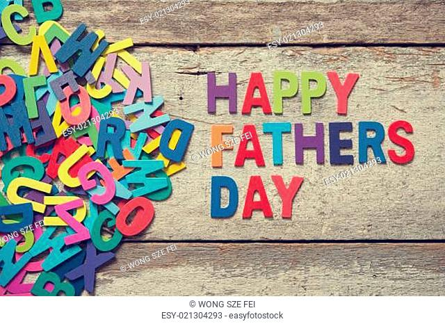"The colorful words ""HAPPY FATHERS DAY"" on old wooden plank"