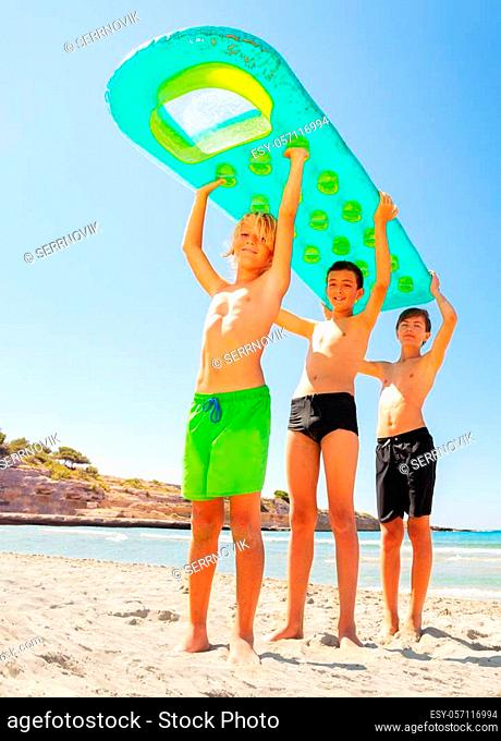 Low-angle shot of three teenage boys, happy friends, holding big air mattress above their heads, standing on sandy beach in summer