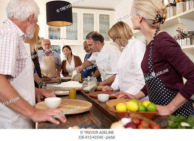 Active senior friends watching chef in pizza cooking class