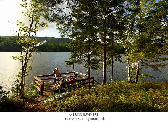 Deck over a lake in late afternoon; Lac-des-Neiges, Quebec, Canada