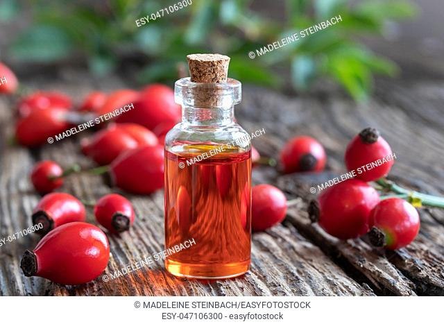 A bottle of rosehip seed oil with fresh berries on a rustic background