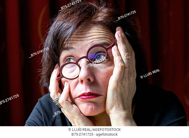 Close-up of middle aged woman with glasses and bored expression