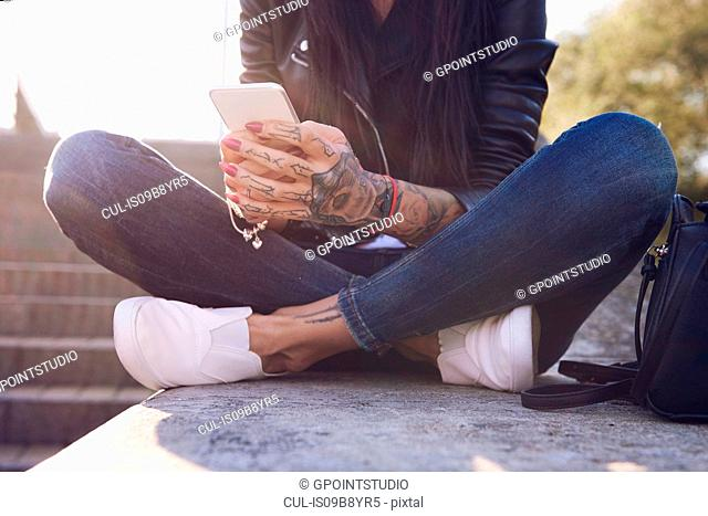 Young woman sitting on wall, using smartphone, tattoos on hand, low section