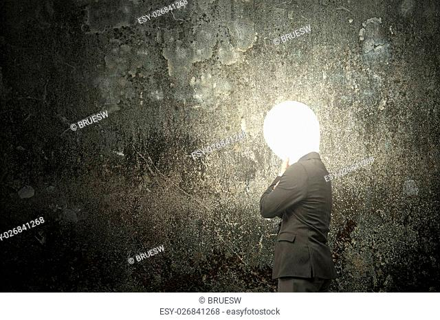 Thinking businessman with lamp head illuminated the dark mottled concrete wall background