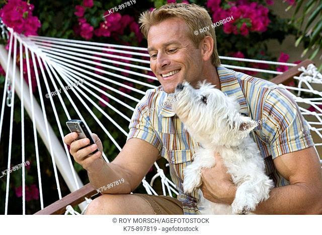 Happy man in hammock with his pet dog