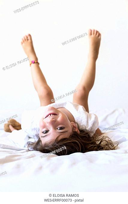 Portrait of happy little girl lying in bed