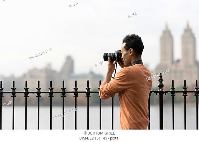 Mixed race man taking photograph on urban waterfront