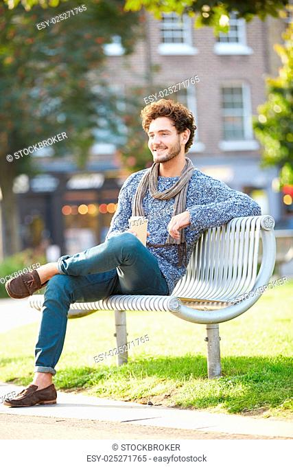 Man Relaxing On Park Bench With Takeaway Coffee