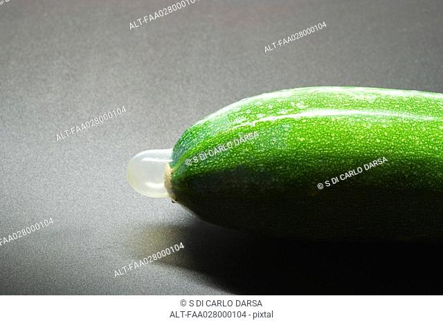 Condom on zucchini, close-up