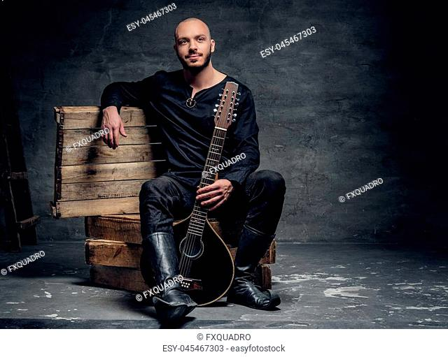 Portrait of a shaved head male musician dressed in old Celtic clothes sits on a wooden box and performing old mandolin