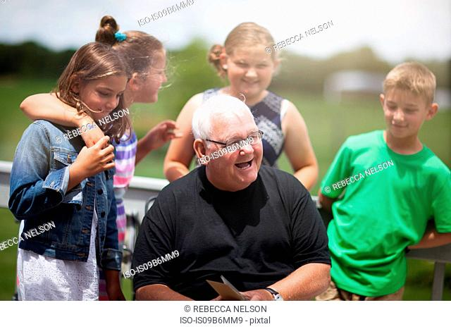 Grandfather surrounded by grandchildren giving him greeting card