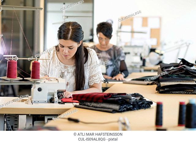 Two seamstresses using sewing machines in workshop