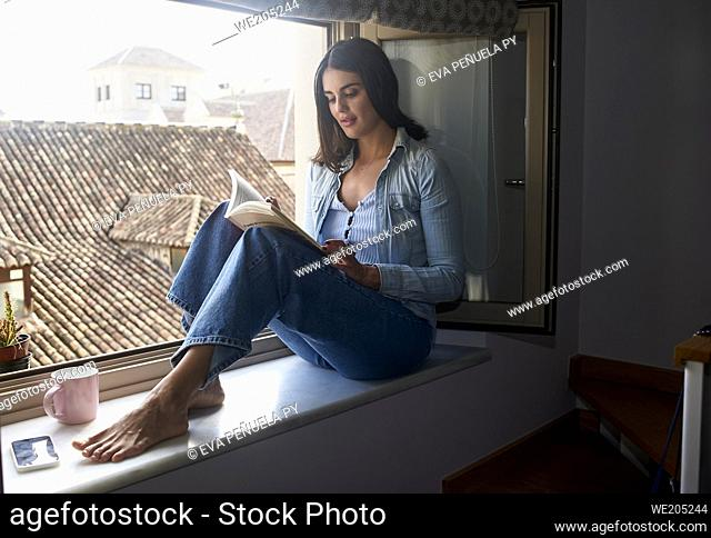 young woman taking a rest, sitting at the window reading