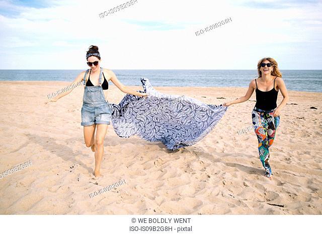 Women dragging picnic blanket on beach, Amagansett, New York, USA