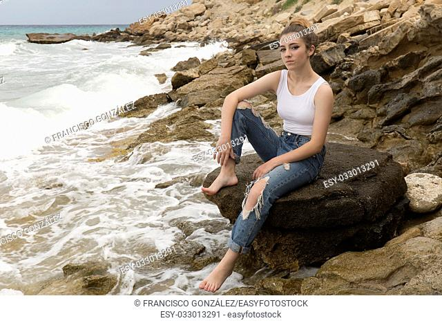Teenage girl sitting on the rocks of a creek of Villajoyosa, in the province of Alicante, Spain