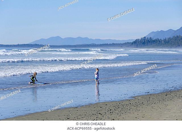 Girls playing in surf, Wickaninnish Beach, in Pacific Rim National Park near Tofino, British Columbia, Canada