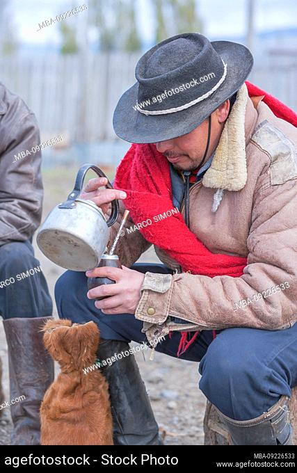 Cowboy pouring mate tea, Torres del Paine National Park, Patagonia, Chile, South America