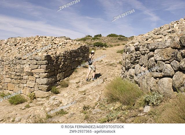 Hiker at the Wall and entrance to the Castro de Ulaca, Villaviciosa, Ávila, Castilla y Leon, Castile, Spain. Vetton village from the Iron Age located at the...