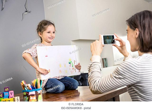Woman photographing daughter with crayon drawing on kitchen table