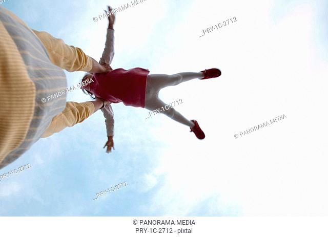 Father lifting his daughter up, upward view