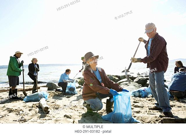 Beach cleanup volunteers picking up litter on sunny beach