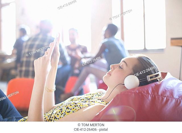 Casual businesswoman relaxing with headphones and digital tablet on bean bag chair