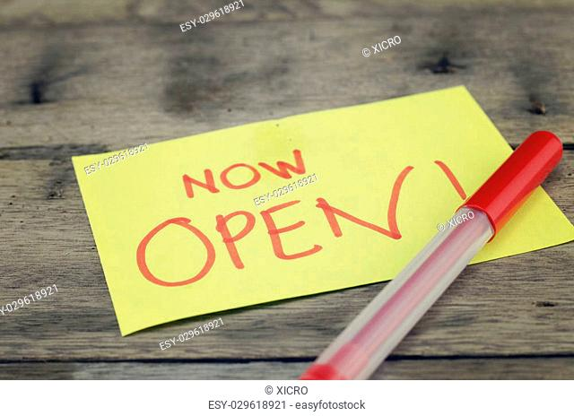 "hand writing sign, """"now open"""" written on yellow sticky paper. dark wooden background with texture. red pen on bottom right"