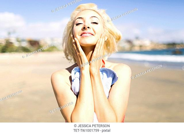Portrait of blond woman on beach applying sun screen