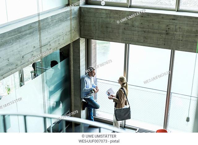 Two colleagues in office talking at the window