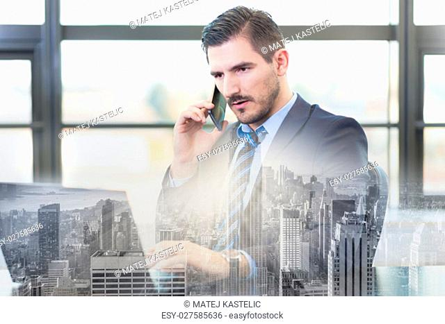 Portrait of successful corporate businessman in bright modern office focused on data on his laptop computer while talking on mobile phone