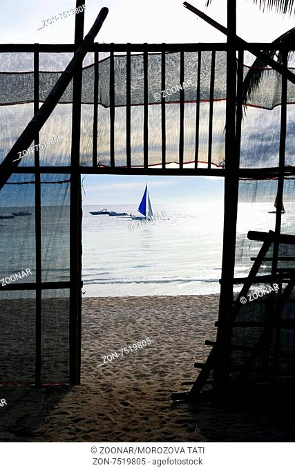Fence on a beach and a drifting sailing boat on a sunset
