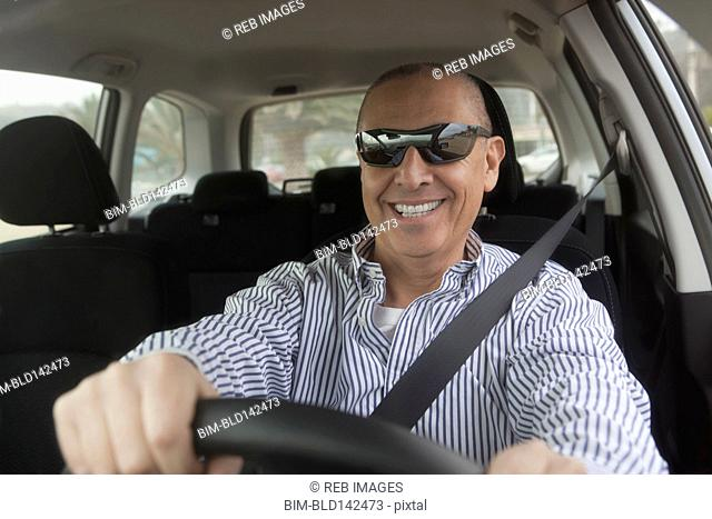 Hispanic senior man in sunglasses driving car