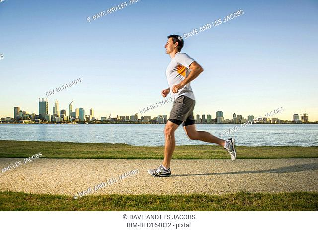 Caucasian man running near urban waterfront, Perth, Western Australia, Australia