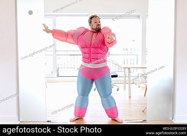 Bouncer in office wearing pink bodybuilder costume