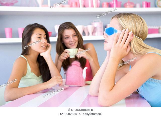 Young woman with a hangover sitting at a table with two friends