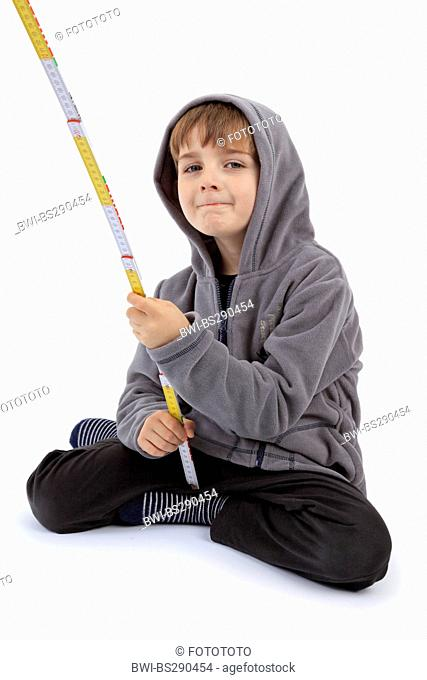little boy playing with a folding rule
