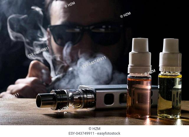 isolated e liquid and vaping device for electronic cigarette with a man wearing sunglasses