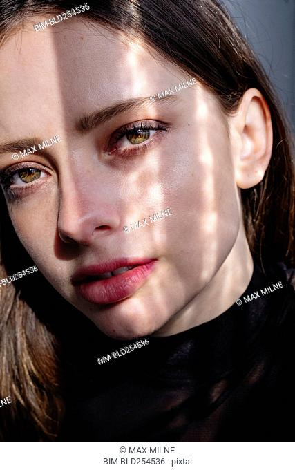 Shadow on face of serious Caucasian woman