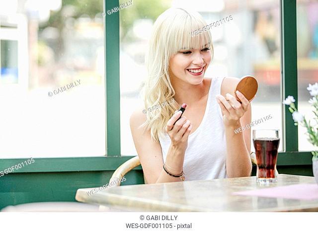 Portrait of blond woman sitting at sidewalk cafe applying lipstick