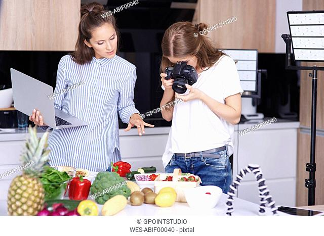 Woman photographing food in kitchen