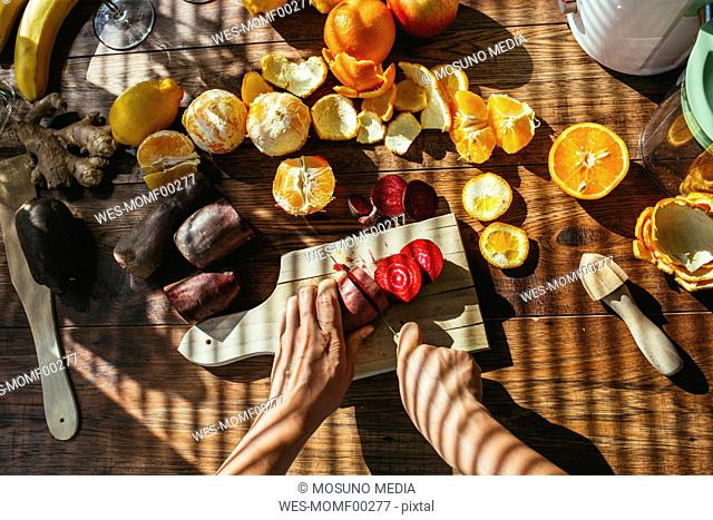 Woman's hands chopping beetroot for squeezing juice