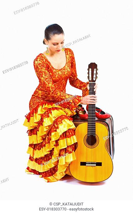 Flamenco dancer sitting on old suitcase with a guitar