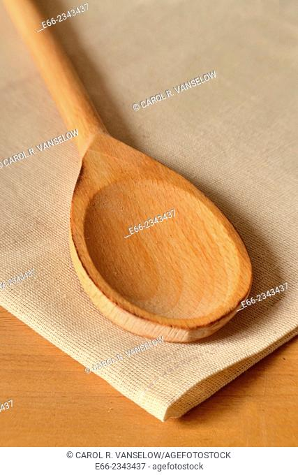 Wooden spoon laying on linen cloth